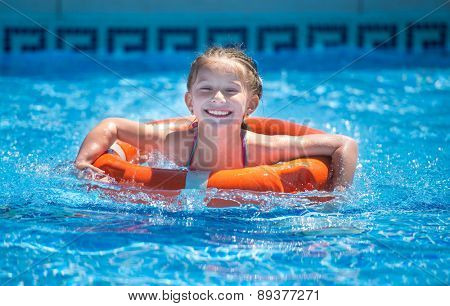 happy little girl swims with a lifeline in the pool in  summer