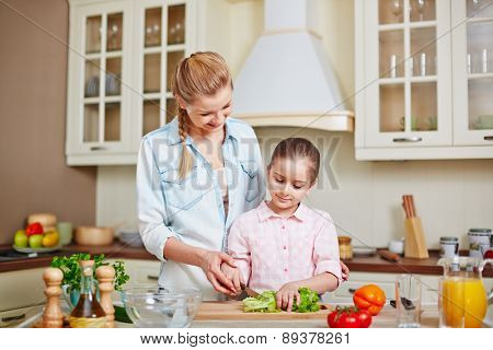 Happy mother and her daughter cooking salad in the kitchen