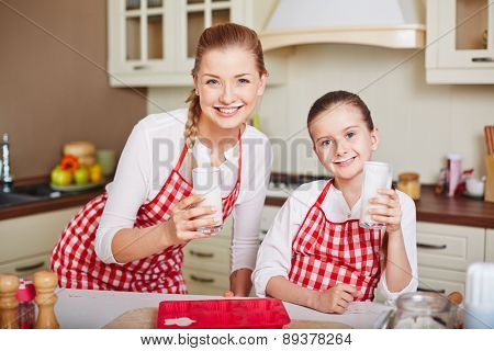 Cute little girl and her mother drinking kefir in the morning