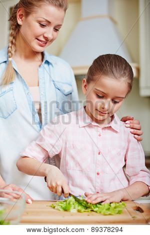Happy woman looking at her daughter cutting lettuce in the kitchen