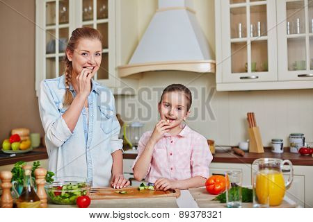Cute girl and her mother eating fresh cucumber in the kitchen