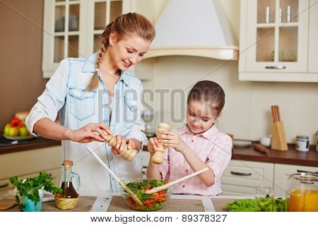 Cute girl and her mother adding salt or spices into bowl with fresh vegetable salad