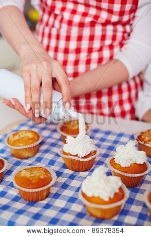 Close-up of young woman decorating baked muffins with whipped cream