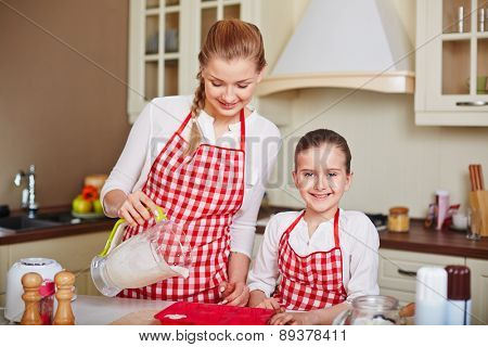 Adorable girl and her mother filling in muffin forms with liquid dough near by
