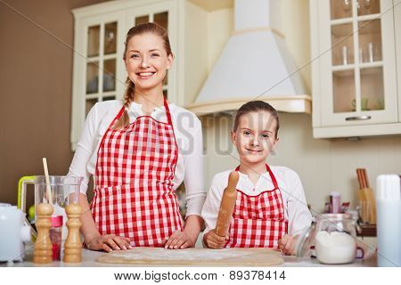 Cute girl and her mother in aprons going to make dough at home