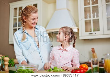 Happy woman and little girl looking at one another while cooking salad at home