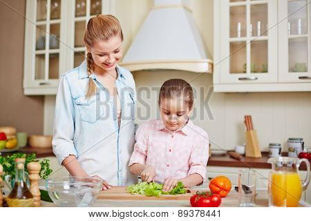Happy woman and her daughter cooking salad together