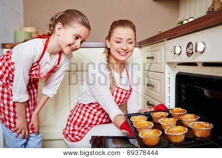 Adorable girl and her mother taking out muffins from oven
