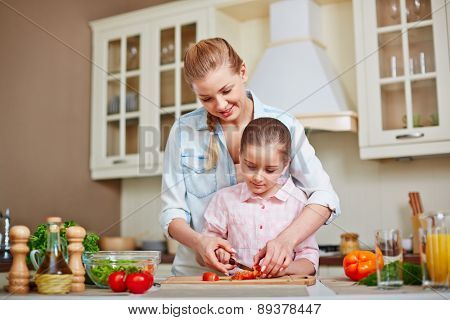 Happy woman and her daughter cutting tomatoes for salad together