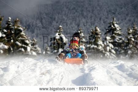 A Little Boy Sledging In The Snow