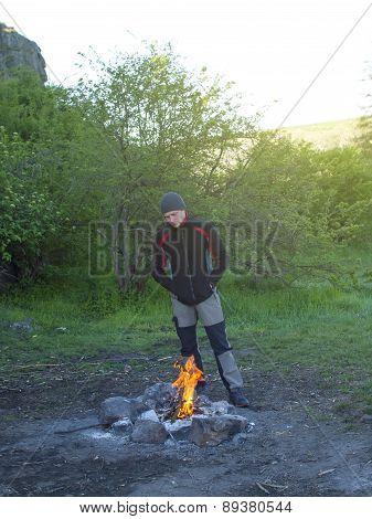 A Man Stands Near A Fire.