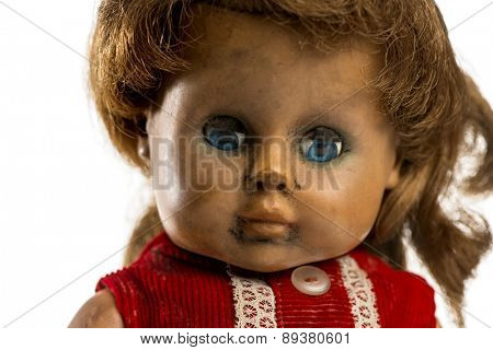Close-up of an used doll in front of a white background