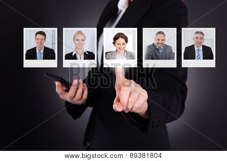 Businesswoman Pointing While Holding Cellphone