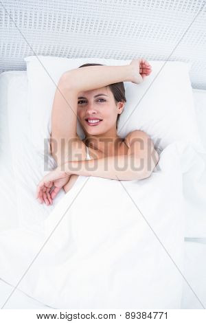 Happy woman in her bed smiling at camera at home in the bedroom