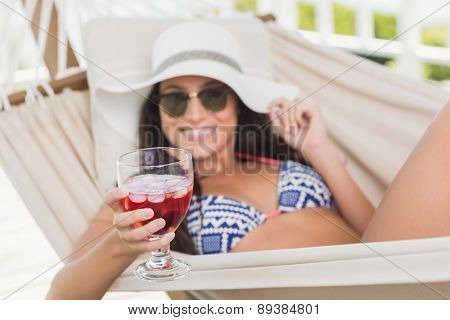 Pretty brunette relaxing on a hammock and drinking cocktail in patio
