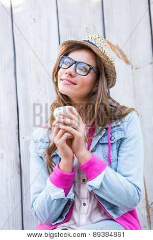 Beautiful woman holding coffee against wooden planks