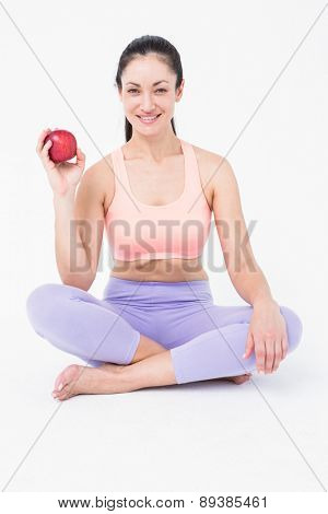 Pretty brunette looking at camera and holding red apple on white background