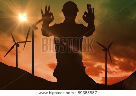 Smiling handyman gesturing okay against sky and mountains