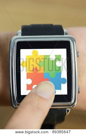 Businesswoman with smart watch on wrist against autism awareness jigsaw