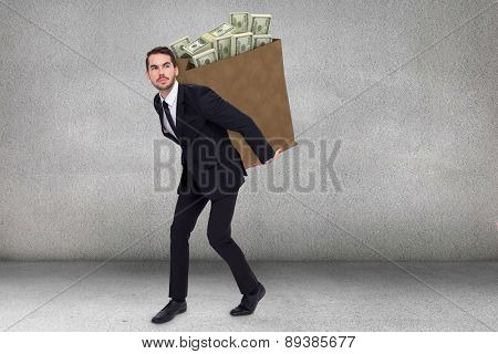 Businessman carrying something with his hands against grey room