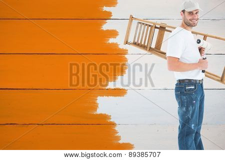 Man with paint roller and step ladder against painted blue wooden planks