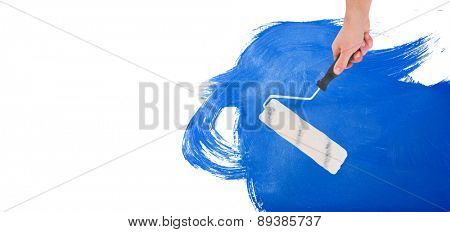 Handyman holding paint roller against blue paint