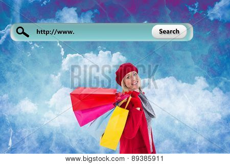Blonde in winter clothes holding shopping bags against painted sky