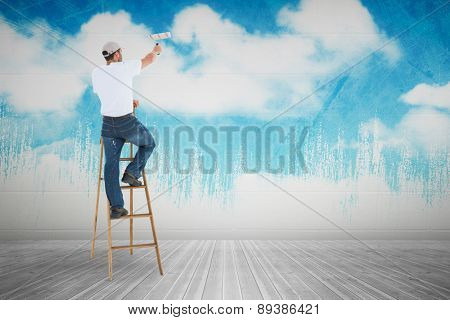 Man on ladder painting with roller against painted sky