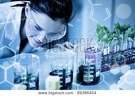 Science graphic against female researcher looking at young plants at lab