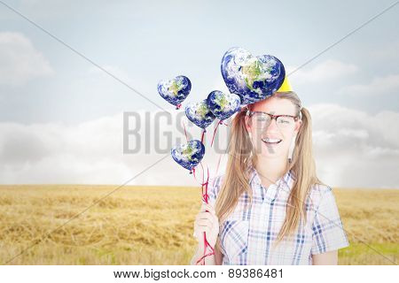 Geeky hipster smiling at camera and holding red balloons against bright brown landscape