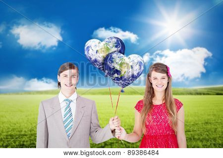 Smiling geeky couple holding red balloons against sunny green landscape