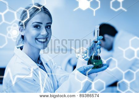 Science graphic against science student holding green chemical in beaker