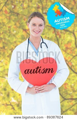 The word autism and doctor holding red heart card against branches and leaves