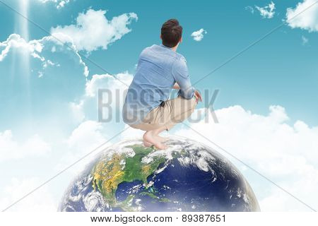 Casual man looking up against blue sky