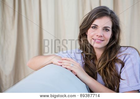 Pretty brunette on couch smiling at camera at home in the living room