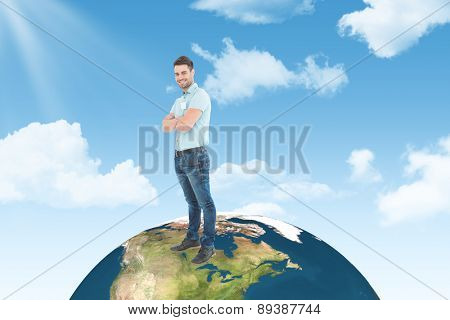 Smiling young delivery man standing arms crossed against blue sky