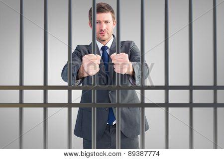 Businessman holding his hands out against grey vignette