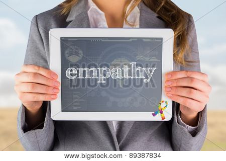 The word empathy and businesswoman showing a tablet pc against medical biology interface in blue