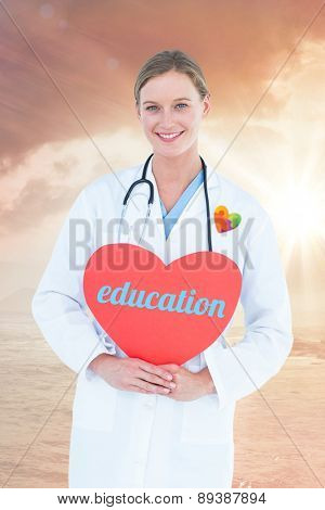 The word education and doctor holding red heart card against sunrise over magical sea