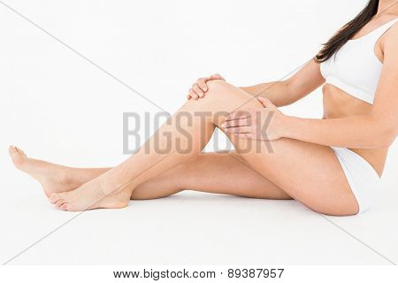 Sitting woman touching her painful knee on white background
