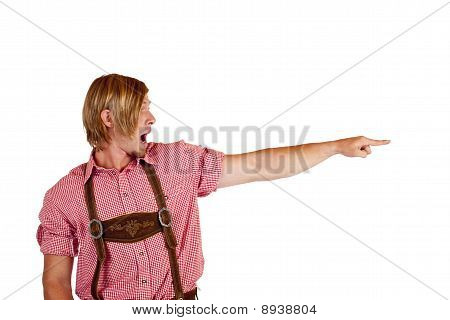 Bavarian man with oktoberfest leather trousers pointing with finger at copy-space.