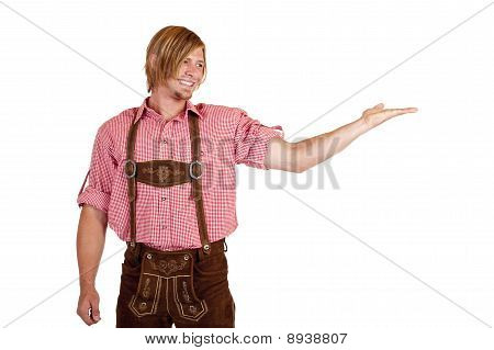 Happy man with oktoberfest leather trousers (lederhose) holds open hand for advertisement.