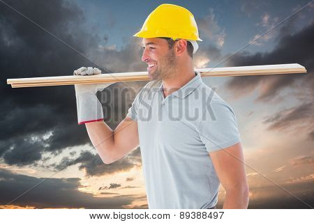 Worker with plank of wood against blue and orange sky with clouds