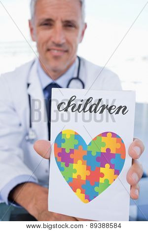 The word children and portrait of a male doctor showing a blank prescription sheet against autism awareness heart