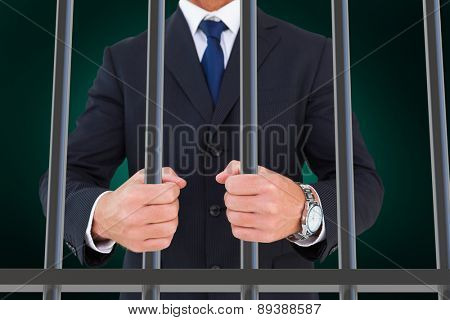 Portrait of a businessman clenching fists against green background with vignette