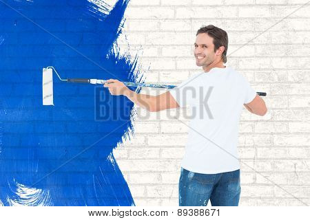 Happy man using paint roller against white wall