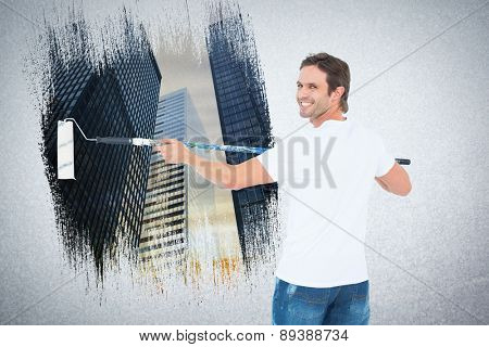 Happy man using paint roller against low angle view of skyscrapers