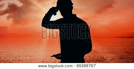 Smiling handyman writing on clipboard against sunrise over field