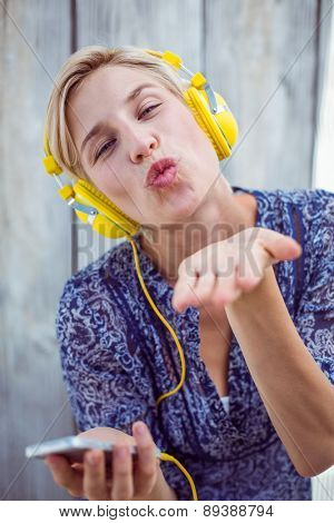 Pretty blonde woman listening music with her mobile phone and blowing kiss on wooden background