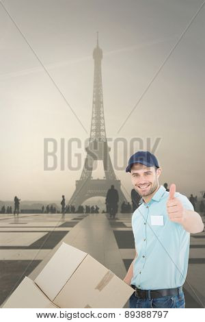 Delivery man with cardboard boxes gesturing thumbs up against eiffel tower